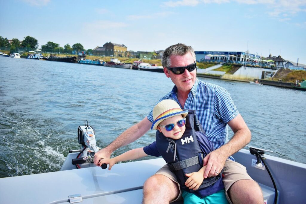 boy steering boat with Daddy on a GoBoat Kingston trip