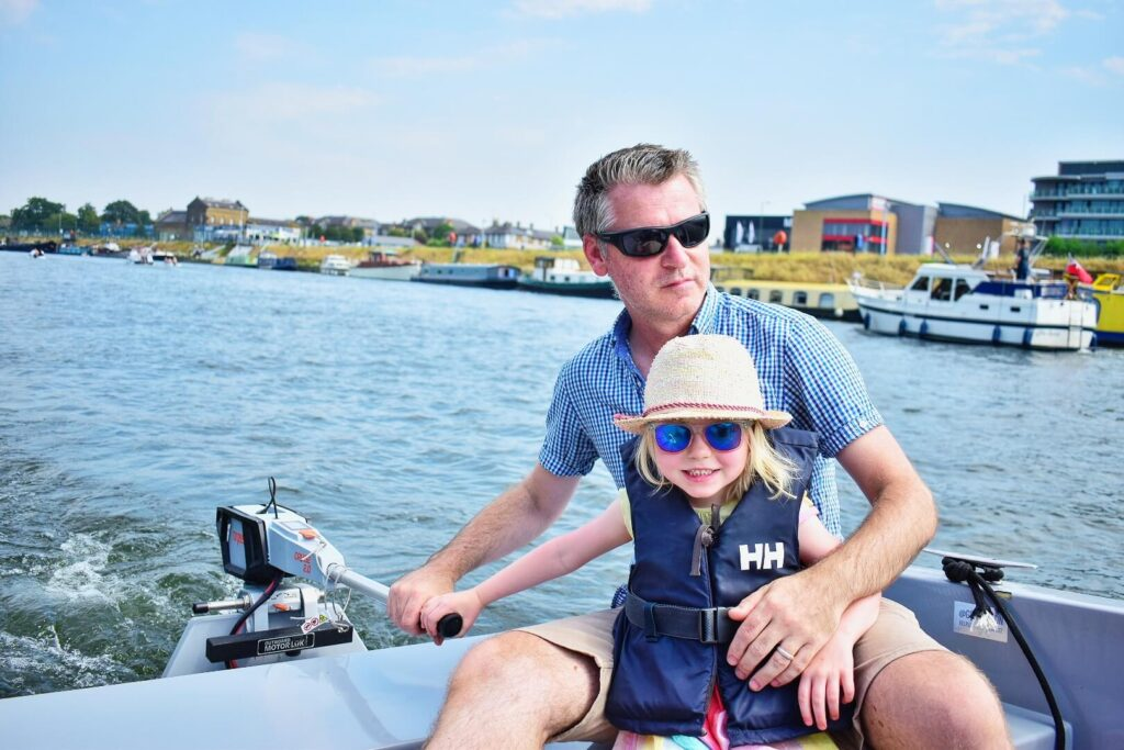 Girl steering boat with Daddy on GoBoat trip