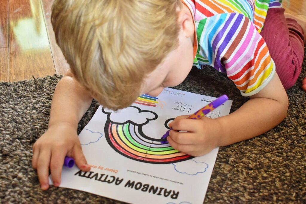 boy colouring a rainbow