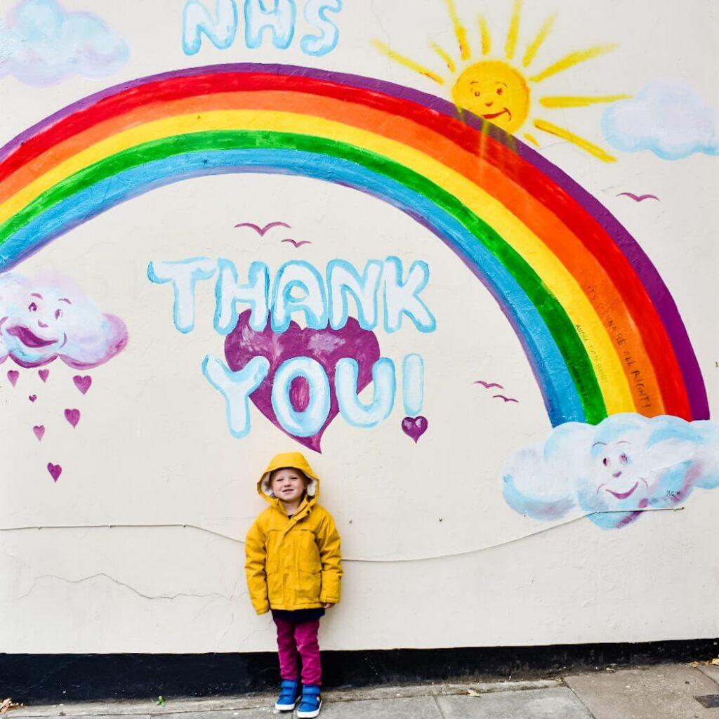 boy in front of rainbow walll