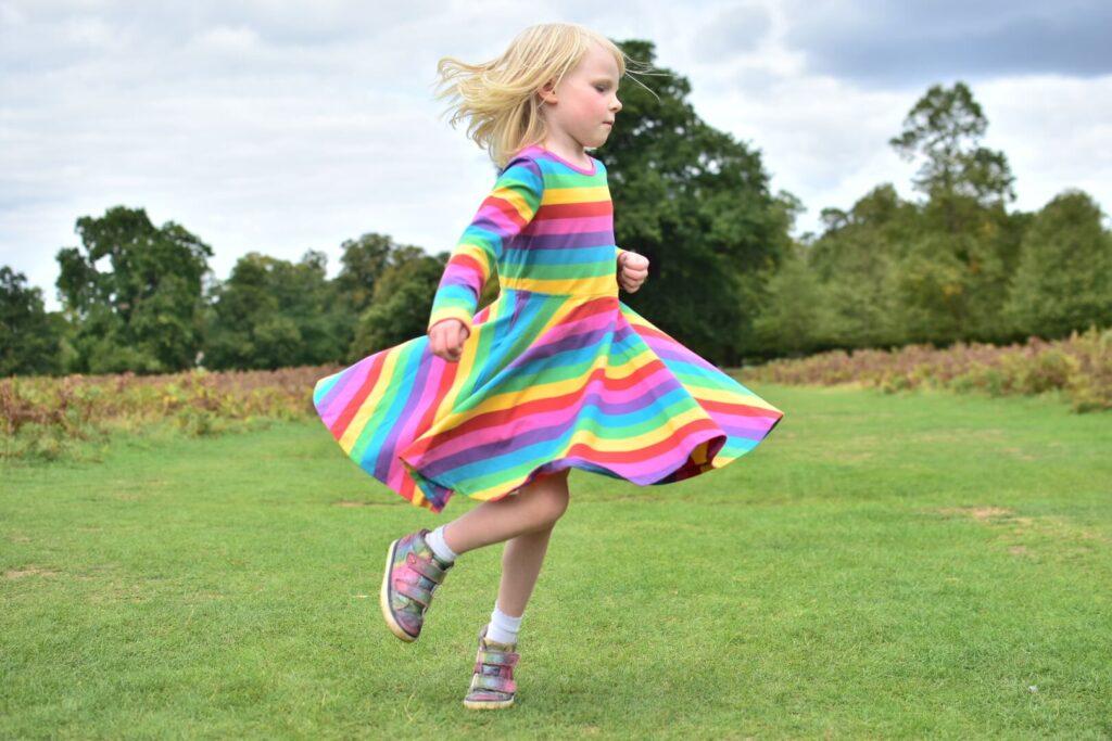 adjusting back into school life girl twirling in rainbow dress