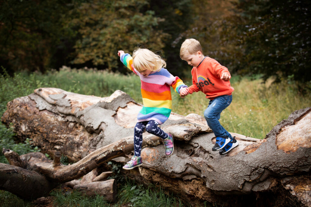 twins jumping from log - family photography Surrey