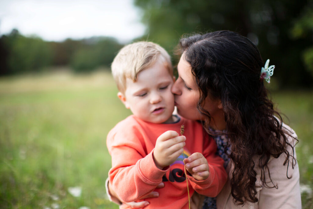Mother kissing son candid family photography Surrey